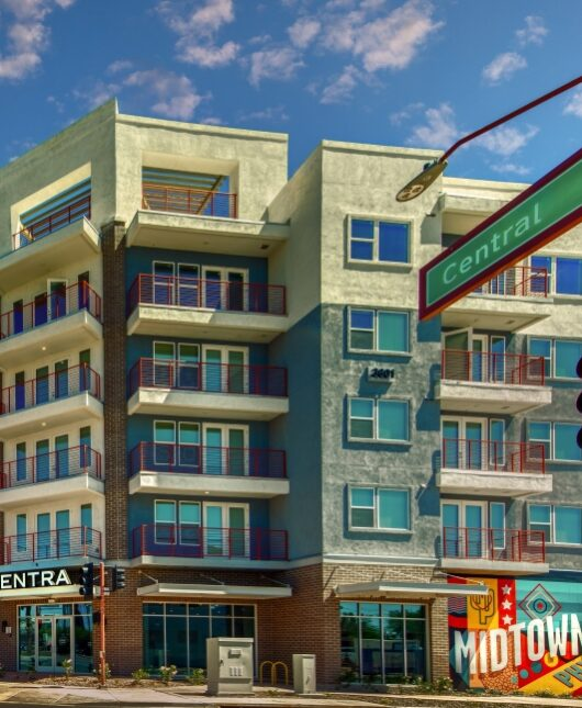 Exterior photo of Centra apartment building. Blue and white with red balconies. Mural in front on ground level.