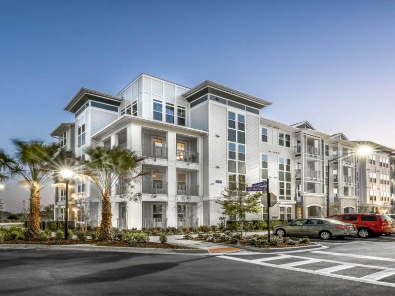 Exterior of Monterosso Apartments at dusk. Four-story white building with blue accents and surface parking.
