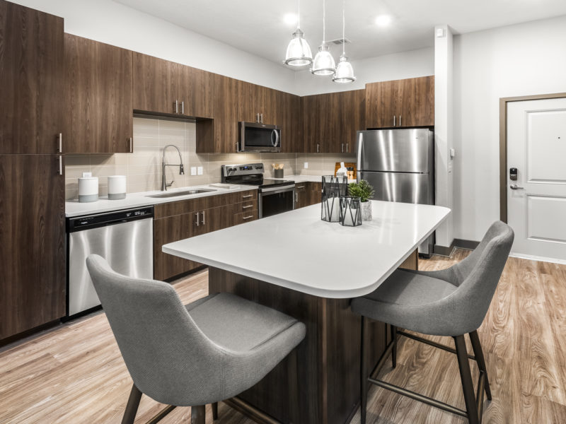 Apartment kitchen with light wide wood-plank style floors, white quartz countertops, kitchen island, dark brown cabinets, tan tile backsplash, and stainless steel appliances.